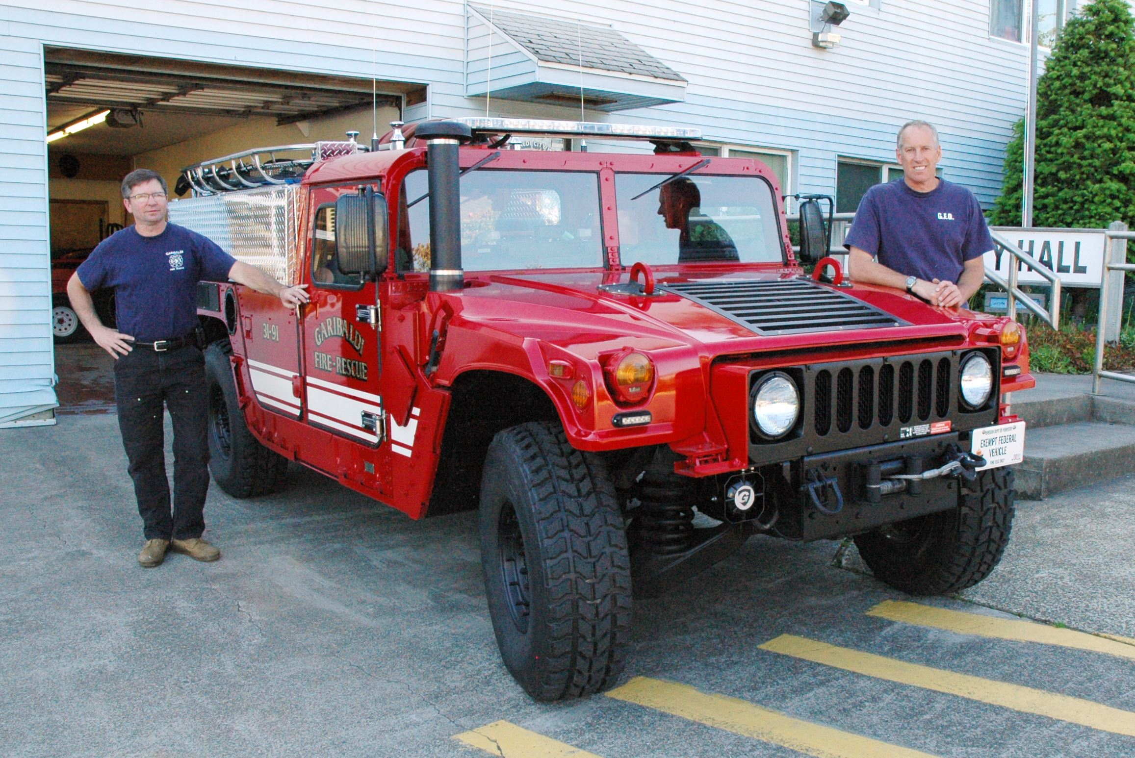 Fire fighters stand beside the Fire Department's Humvee